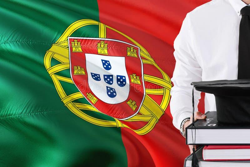 Conceito português bem sucedido da educação do estudante Guardando livros e tampão da graduação sobre o fundo da bandeira de Port fotografia de stock