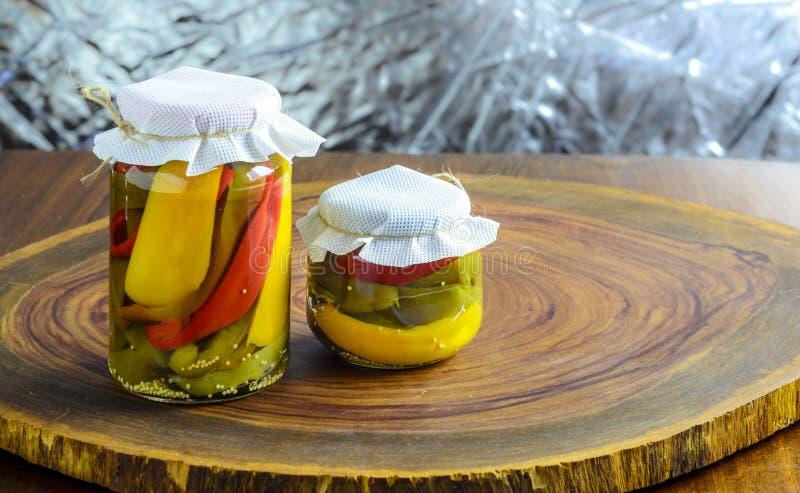 Conceito preservado do alimento do vegetariano Vermelho enlatado, verde pimentas amarelas em um frasco no fundo de madeira imagem de stock