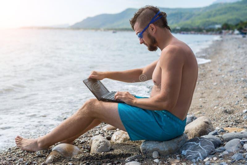 Conceito remoto do trabalho: Homem de negócio que trabalha em um portátil ao relaxar na praia fotografia de stock