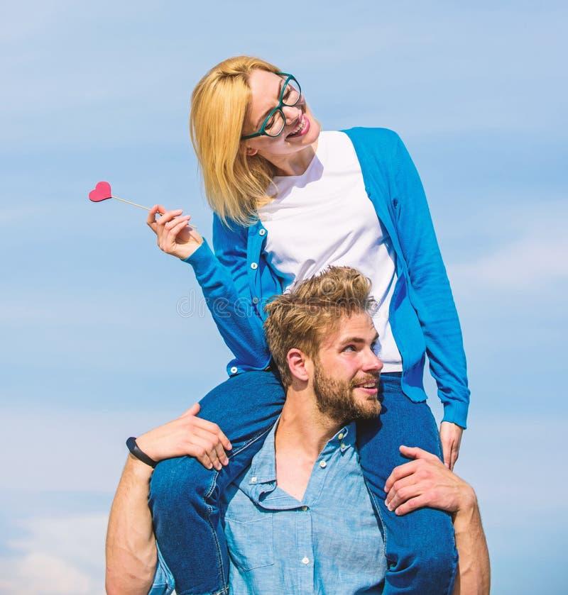 Conceito romântico da data O homem leva a amiga em ombros, fundo do céu Data feliz dos pares que tem o divertimento junto Mulher fotos de stock
