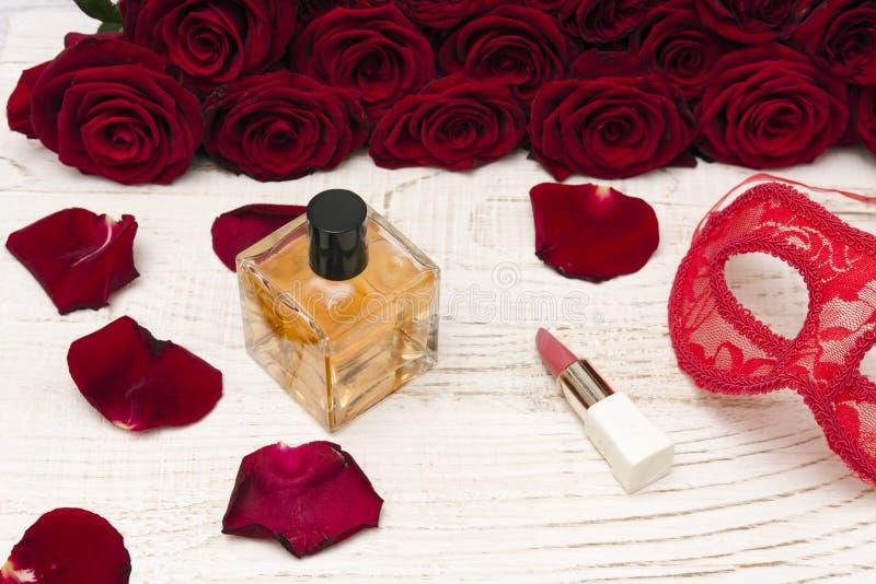 Conceito romântico do carnaval Máscara vermelha do carnaval, ramalhete de rosas vermelhas, batom e garrafa do perfume no fundo de fotografia de stock royalty free