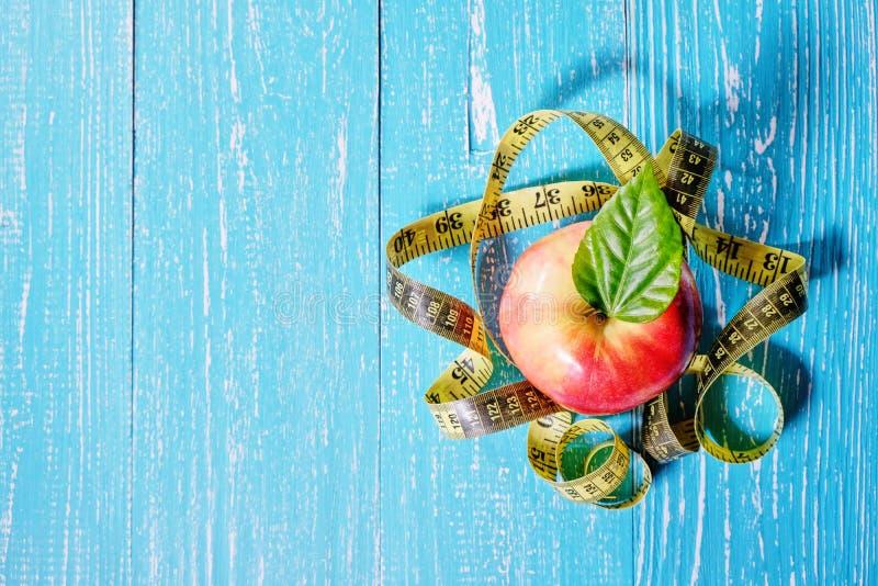 Conceito saudável do alimento Apple e fita métrica no fundo de madeira foto de stock