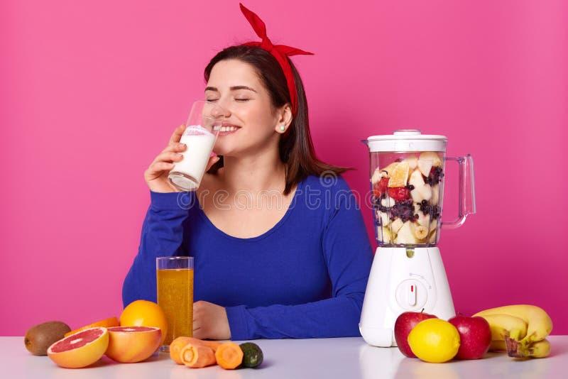 Conceito saudável do alimento, da nutrição e dos vitamnis A mulher satisfeita prepara o suco de fruto no misturador, bebe o leite imagem de stock