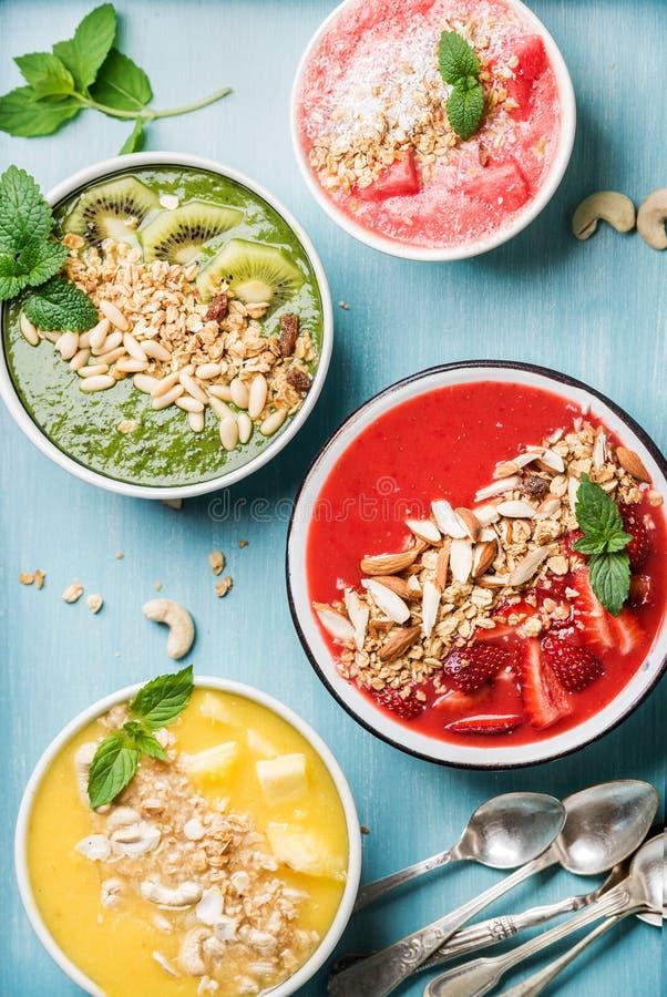 Conceito saudável do café da manhã do verão Bacias coloridas do batido de fruta no fundo do azul de turquesa imagens de stock royalty free