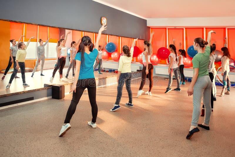 Conceito saudável do estilo de vida das crianças - grupo de desportivo dos adolescentes que exercitam no gym fotos de stock