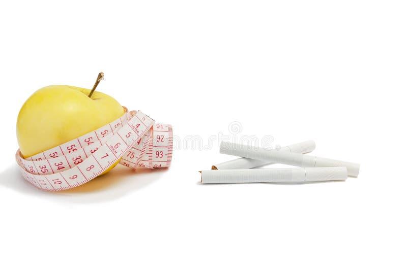 Conceito saudável do estilo de vida Fita de medição com uma maçã amarela e cigarros em um fundo branco isolate imagens de stock royalty free