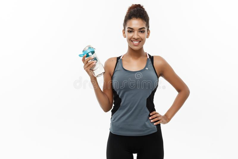 Conceito saudável e da aptidão - a menina afro-americano bonita no esporte veste guardar a garrafa de água após o exercício fotos de stock