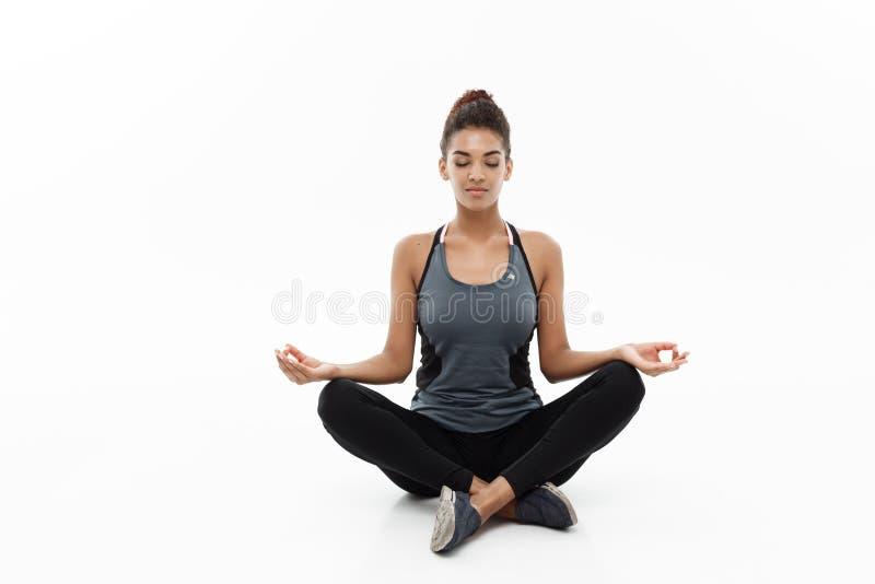 Conceito saudável e da aptidão - senhora africana americana bonita na roupa da aptidão que faz a ioga e a meditação isolado sobre foto de stock