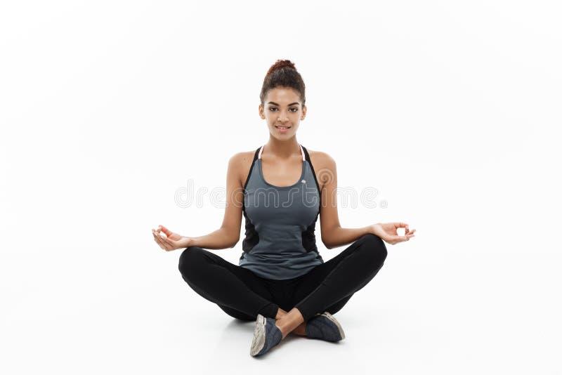 Conceito saudável e da aptidão - senhora africana americana bonita na roupa da aptidão que faz a ioga e a meditação isolado sobre fotografia de stock royalty free