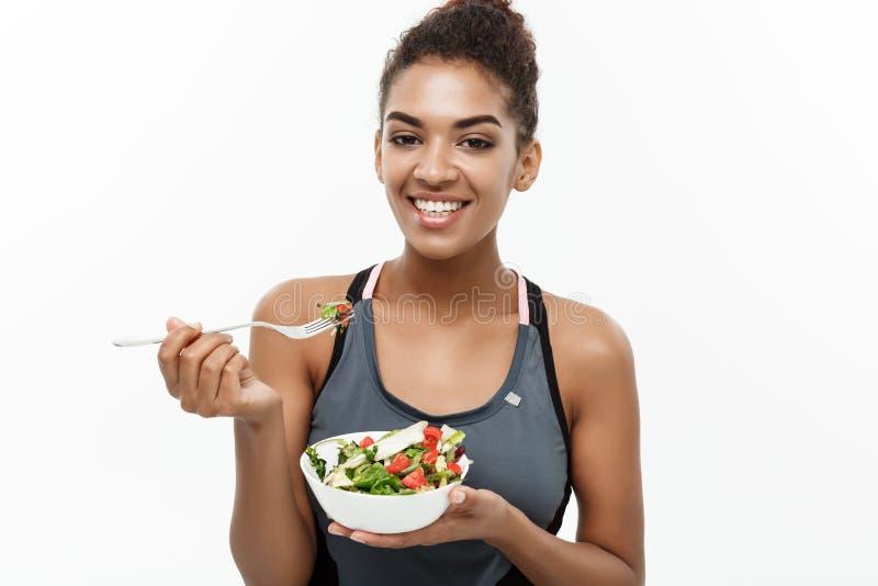 Conceito saudável e da aptidão - a senhora africana americana bonita na aptidão veste-se na dieta que come a salada fresca isolad foto de stock royalty free