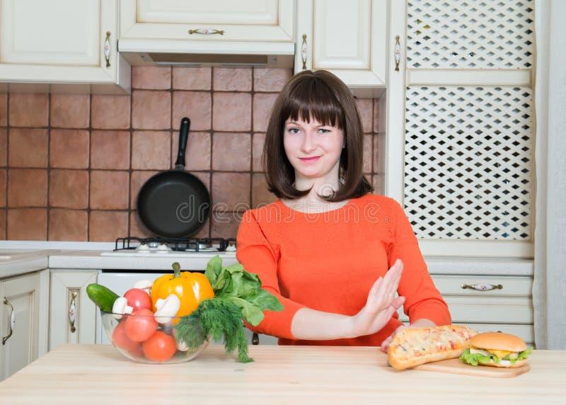 Conceito saudável e da comida lixo - mulher com rejeição dos vegetais foto de stock