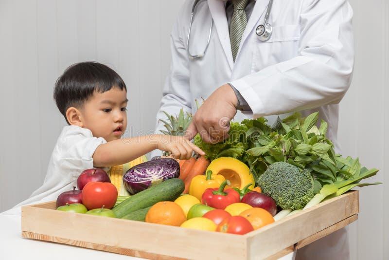 Conceito saudável e da nutrição Caçoe a aprendizagem sobre a nutrição com doutor escolher comer frutas e legumes frescas fotos de stock