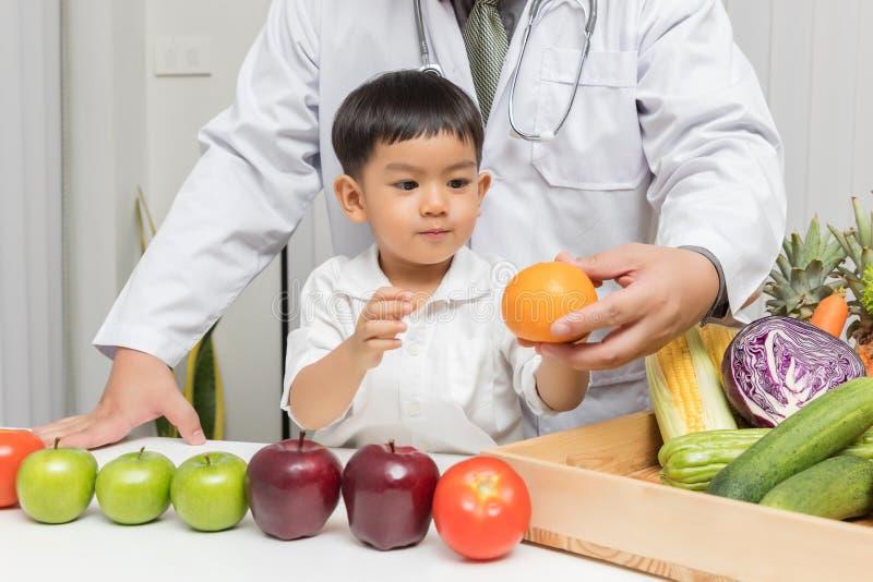 Conceito saudável e da nutrição Caçoe a aprendizagem sobre a nutrição com doutor escolher comer frutas e legumes frescas Asiático imagens de stock