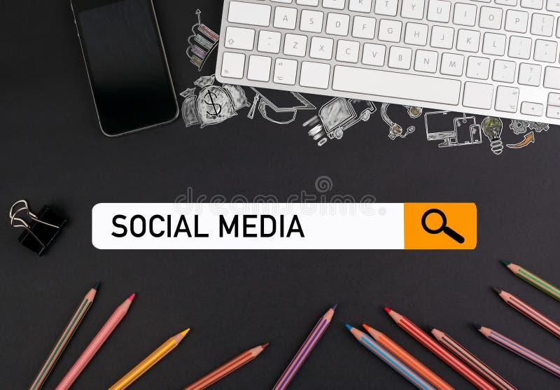Conceito social dos media lápis coloridos e um teclado de computador com um telefone celular em uma tabela preta foto de stock