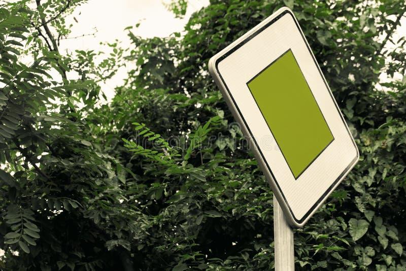 Conceito surreal do sinal de tráfego da cor verde com folha luxúria - o social emite o conceito com espaço da cópia Close-up do s foto de stock royalty free