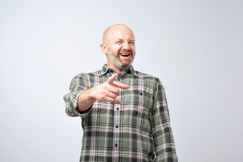 Conceito trocista ou mau do gracejo Homem maduro que aponta o dedo e o sorriso toothy imagens de stock royalty free