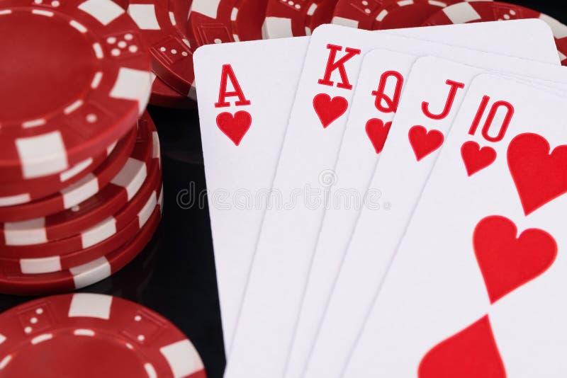 Conceito vermelho das microplaquetas de pôquer e dos cartões de jogo no fim preto do fundo acima foto de stock royalty free