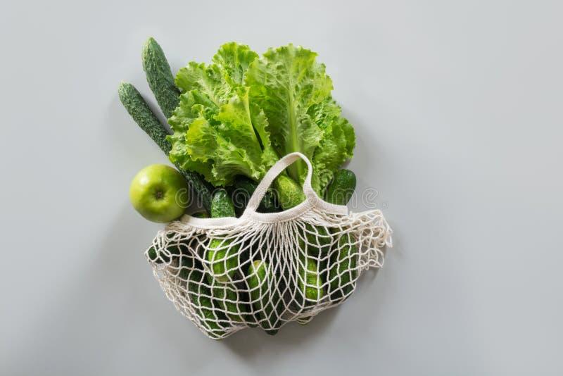 Conceito waste zero Saco de compra moderno de matéria têxtil três com os vegetais verdes frescos Vista de acima imagem de stock royalty free