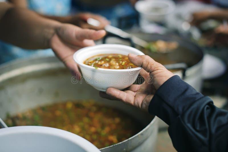 Conceitos de alimentação: A mão ofereceu doar o alimento de uma parte do homem rico: O conceito da partilha social: Povos pobres  imagens de stock royalty free