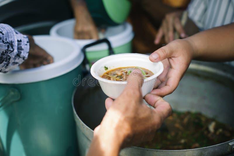 Conceitos de alimentação: A mão ofereceu doar o alimento de uma parte do homem rico: O conceito da partilha social: Povos pobres  foto de stock