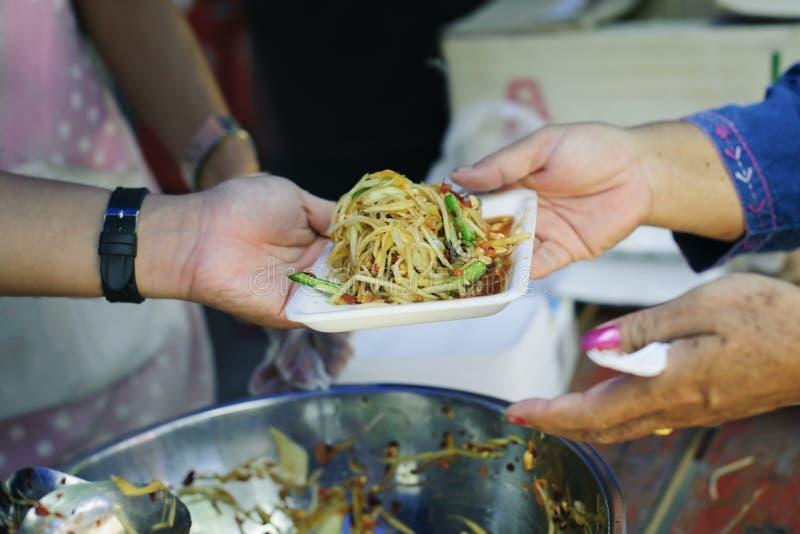 Conceitos de alimentação: A mão ofereceu doar o alimento de uma parte do homem rico: O conceito da partilha social: Povos pobres  imagem de stock