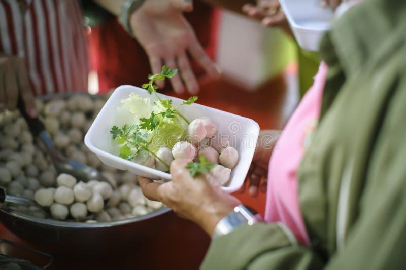 Conceitos de alimentação: A mão ofereceu doar o alimento de uma parte do homem rico: O conceito da partilha social: Povos pobres  fotografia de stock