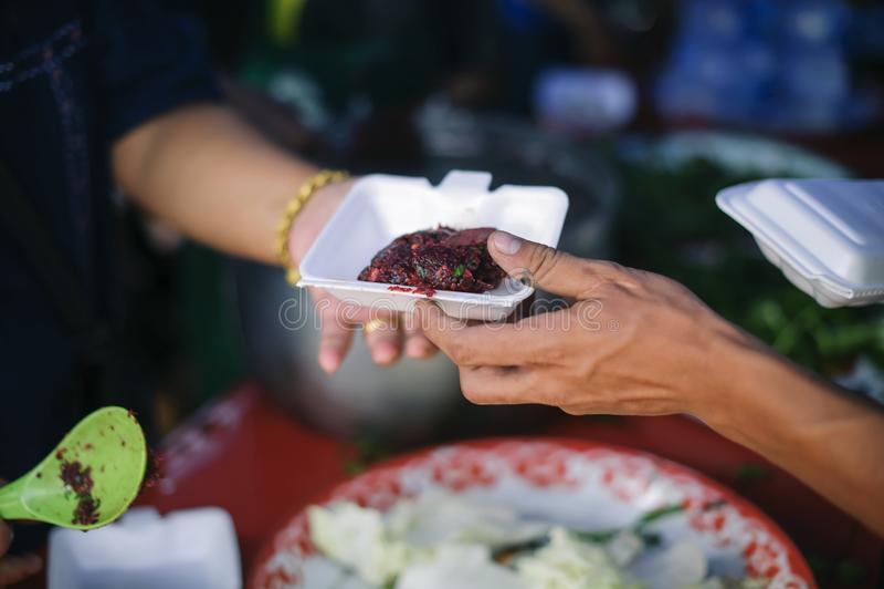 Conceitos de alimentação: A mão ofereceu doar o alimento de uma parte do homem rico: O conceito da partilha social: Povos pobres  imagem de stock royalty free