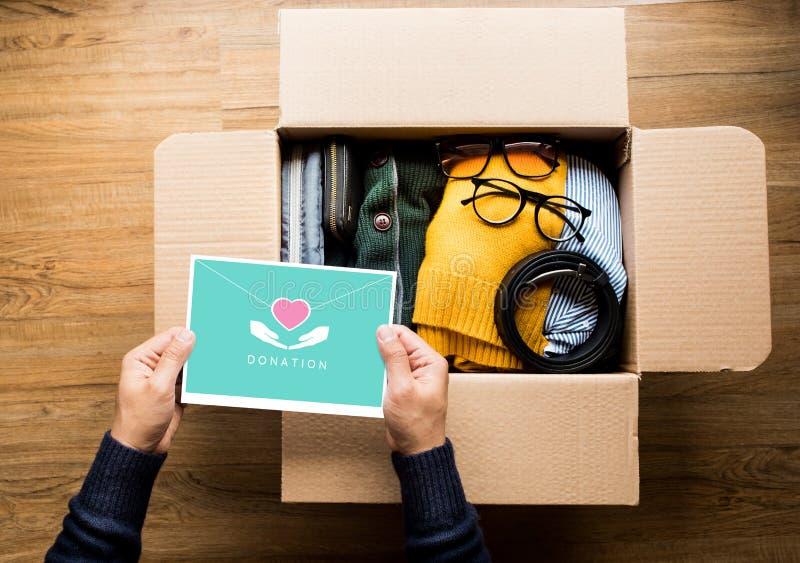 Conceitos de doação com a pessoa que tem o cartão de correio direto no vestuário dos acessórios doação e partilha com seres human imagem de stock