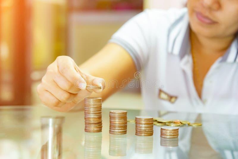Conceitos de salvamento do dinheiro, mulher que empilha moedas em colunas crescentes fotografia de stock royalty free