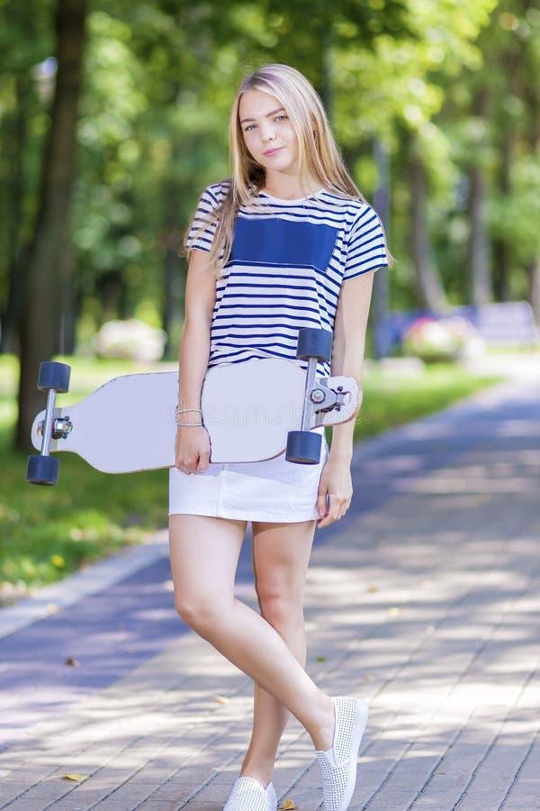 Conceitos do estilo de vida do adolescente Menina loura caucasiano de sorriso feliz do adolescente que levanta com Longboard fora foto de stock royalty free