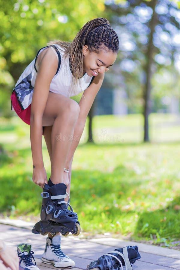 Conceitos do estilo de vida do adolescente O adolescente afro-americano põe sobre patins de rolo no parque fora foto de stock royalty free