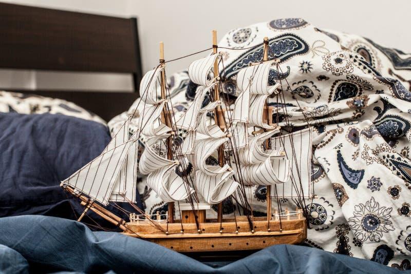 Conceitos do negócio e da faculdade criadora modelo de um navio de navigação em um fundamento azul imagem de stock royalty free