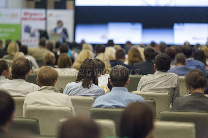 Conceitos do negócio Grande grupo de pessoas nas cartas de observação da apresentação da conferência na tela fotos de stock royalty free