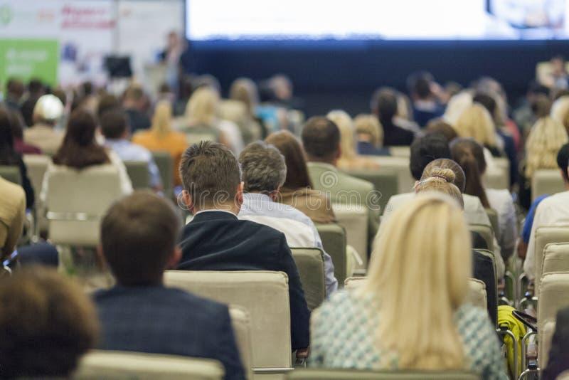 Conceitos do negócio Grande grupo de pessoas nas cartas de observação da apresentação da conferência na tela na frente delas imagem de stock royalty free