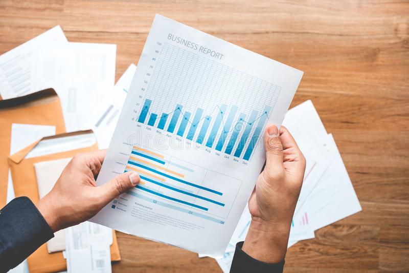 Conceitos do sucesso comercial com o homem de negócios que guarda o gráfico do relatório do papel imagens de stock royalty free