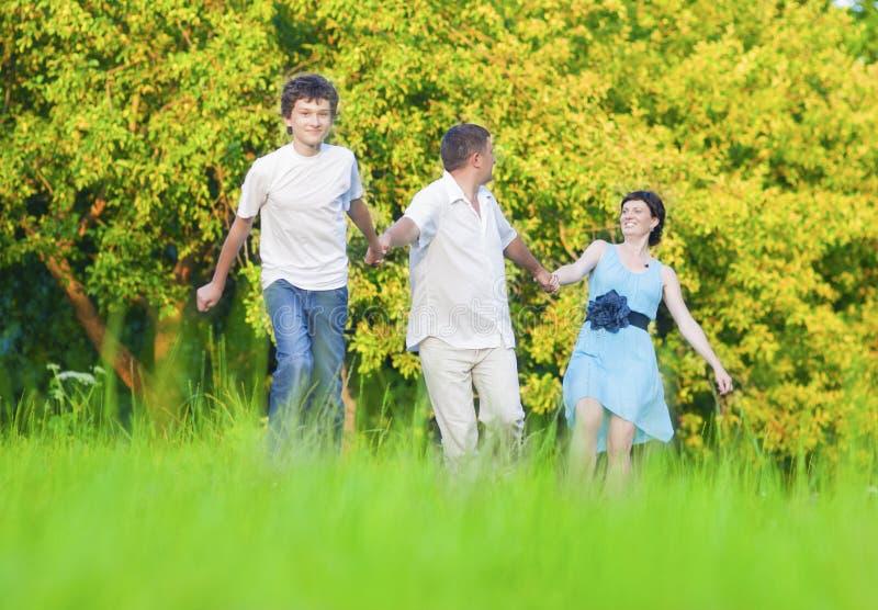 Conceitos e ideias dos valores familiares Família de três caucasiano que têm o divertimento junto e que correm na floresta do ver imagens de stock royalty free