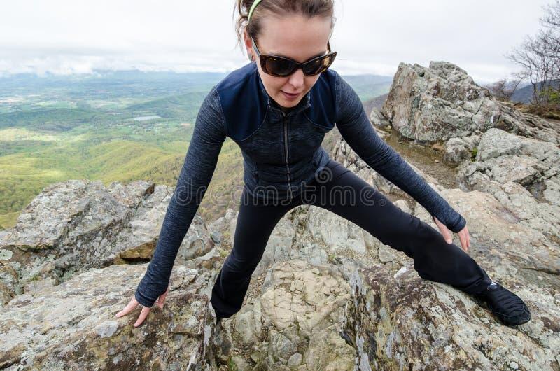 Concentrés de randonneur de femme et de grimpeur de roche sur brouiller vers le haut d'une section raide des outcroppings de roch photographie stock