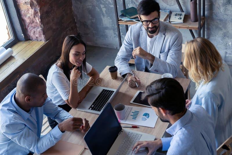 Concentração completa no trabalho Grupo de executivos novos que trabalham e que comunicam-se ao sentar-se na mesa de escritório imagens de stock