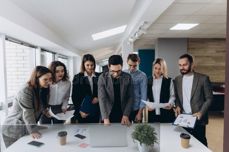 Concentración completa en el trabajo Grupo de hombres de negocios jovenes que trabajan y que comunican mientras que se coloca en  imagen de archivo