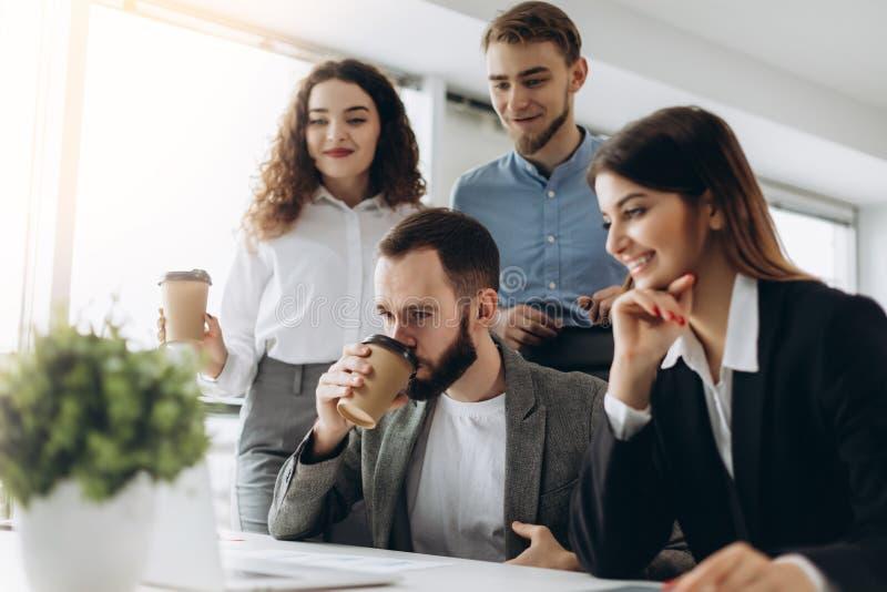 Concentración completa en el trabajo Grupo de hombres de negocios jovenes que trabajan y que comunican mientras que se sienta en  foto de archivo