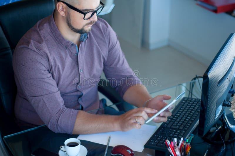 Concentrado en trabajo Funcionamiento joven concentrado del hombre de la barba Busi fotografía de archivo libre de regalías