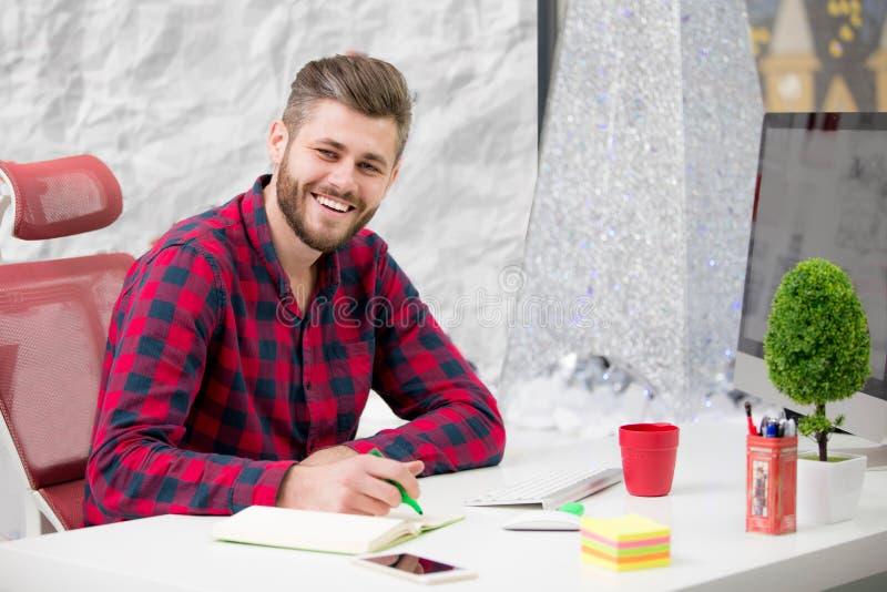 Concentrado no trabalho Homem novo concentrado da barba que trabalha no portátil ao sentar-se em seu lugar de funcionamento no es fotografia de stock