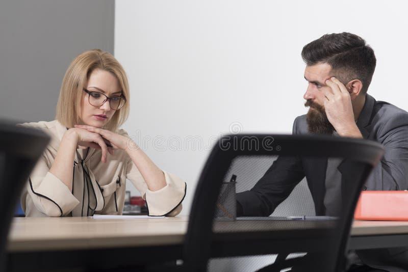 Concentrado no trabalho A mulher e o homem trabalham junto na mesa A mulher de negócios e o homem de negócios têm a reunião de ne imagem de stock