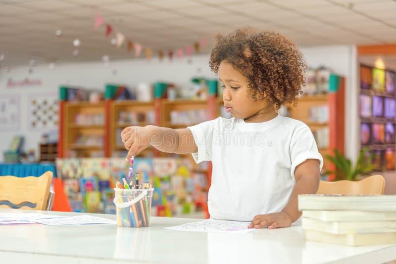 Concentrado pequeno da menina da criança no desenho Menina africana da mistura para aprender e jogar na classe do pré-escolar As  fotografia de stock