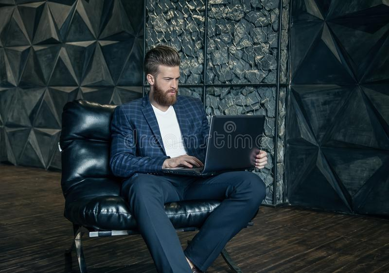 Concentraiting on project. Thoughtful young modern man using computer while sitting at his working place royalty free stock image