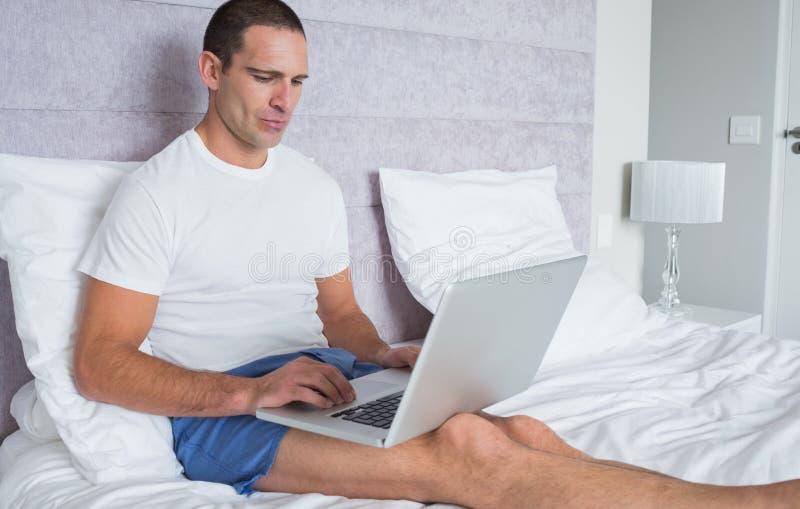 Concentrando uomo che per mezzo del computer portatile sul letto fotografia stock