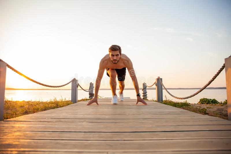 Concentrared young sportsman is ready to run outdoors in the morning. royalty free stock photography