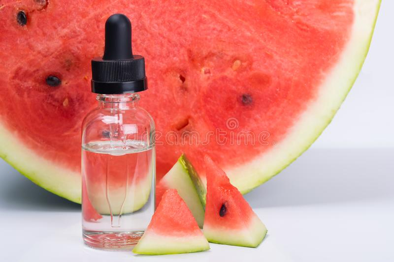 Concentrate of watermelon flavor in a bottle, next to it royalty free stock image