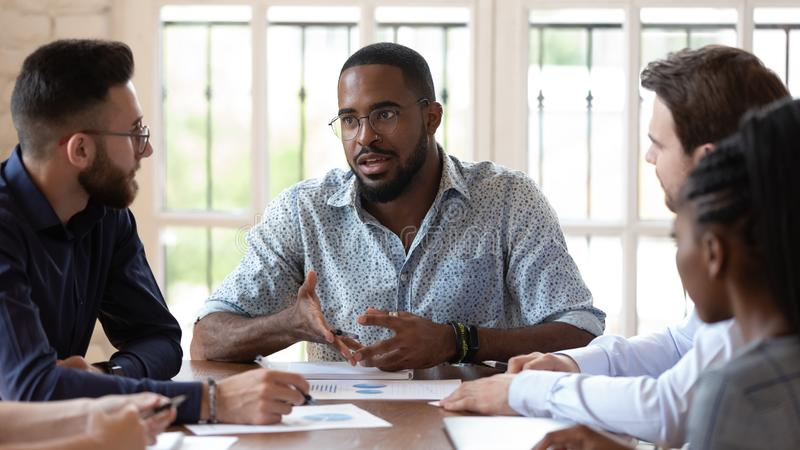 Concentrated african amrican male manager talking to diverse colleagues. stock photography
