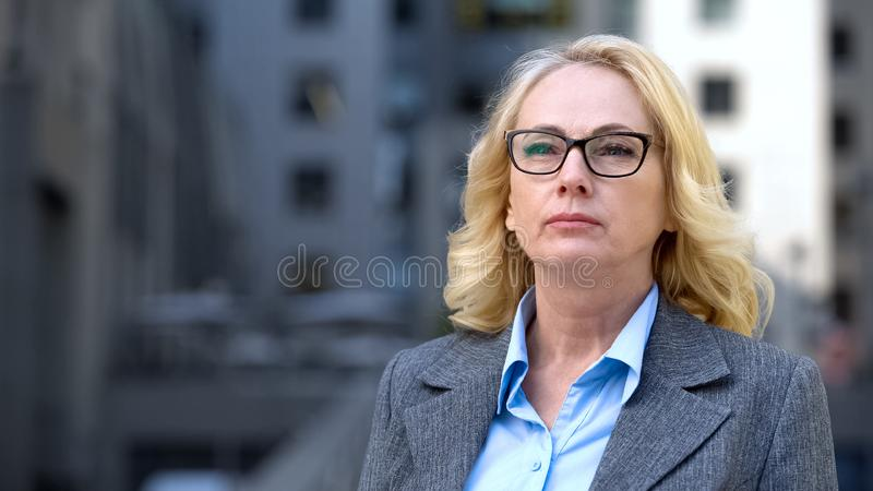 Concentrated aged business woman eyeglasses thinking of work, company strategy stock photo